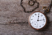 Old gold pocket watch on a chain on an old wooden — Stock Photo