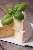 Brie cheese on old wooden table with green basil — Stock Photo