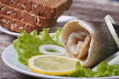 Pickled herring roll with onion on lettuce, lemon and bread — Stock Photo