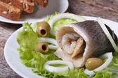 Herring roll with onion rings, olives and bread — Stock Photo