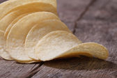 Curved potato chips on an old table — Stock Photo