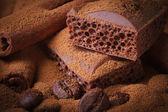 Aerated chocolate, coffee beans and cinnamon sticks closeup — Stock Photo