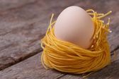 Dried pasta in the shape of the nest with chicken eggs — Stock Photo