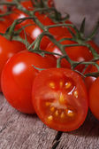 Branch of ripe tomatoes and one sliced ??fruit close up — Stock Photo