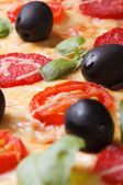 Texture of pizza with salami, tomato, olives macro. — Stock Photo