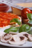 Preparation of ingredients for pizza: sliced ??mushrooms, basil — Stock Photo