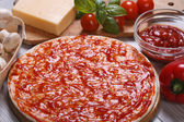 Basis for pizza with tomato sauce and ingredients — Stock Photo