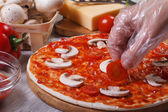 Hand in glove chef puts on a pizza base cherry tomatoes. — Stock Photo