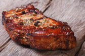 Grilled pork steak with spices and herbs on an old board — Foto Stock