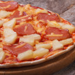 Hawaiian pizza with pineapple and ham on an old wooden table — Stock Photo