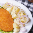 Stock Photo: Schnitzel with young boiled potatoes on a white plate closeup