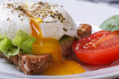 Open poached egg, tomato and bread — Stock Photo