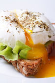 Open poached egg, salad and bread vertical macro — Stock Photo