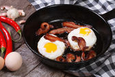 Fried eggs with bacon in a skillet — Foto de Stock