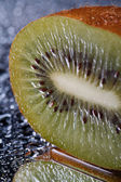 Half kiwi with water drops macro  vertical  — Foto de Stock