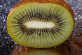 Half kiwi with water drops close-up. — Foto de Stock