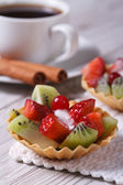 Tartlets with strawberries and kiwi with a cup of coffee — Foto de Stock