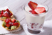 Yogurt with fresh strawberries and fruit tartlets closeup  — Foto de Stock