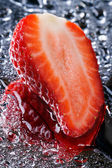 Half of fresh strawberries with water vertical. Macro — Stock Photo