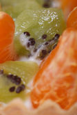 Pieces of kiwi and tangerine slices with cream macro — Stock Photo