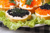 Sandwiches with red and black caviar on lettuce  — Stock Photo