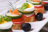 Various banquet canape with salmon, eggs, vegetables — Stock Photo