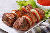 Delicious grilled shish kebab with vegetables and sauce — Stock Photo