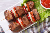 Shashlik with vegetables and sauce top view — Stock Photo