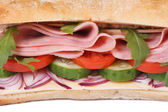 Sandwich with ham, fresh vegetables and arugula isolated macro. — Stock Photo