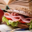 Sandwich with ham and vegetables and red apple on open notebook — Stock Photo
