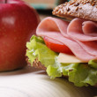 Sandwich with ham and vegetables and red apple vertical — Stock Photo #44124317