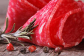 Rolled salami macro with rosemary and pepper.  — Stock Photo