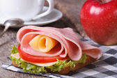 Beautiful sandwich with ham and cheese, coffee, red apple — Stock Photo