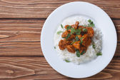 Chicken curry with rice and cilantro on a plate top view — Stock Photo