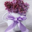 Delicate flowers of lilac in a white jug with a bow — Stock Photo #46079931