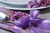 table setting decorated with fragrant lilac flowers — Stock Photo