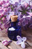 Extract from the fragrant lilac flowers close up on the table — Stock Photo