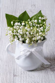 Beautiful bouquet of lilies of the valley in a white jug — Stock Photo