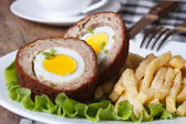By scotch egg and fried potatoes close-up — Stock Photo