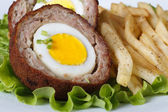 By scotch egg and fried potatoes macro — Stock Photo