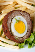 By scotch egg with french fries macro. Vertical — Stock Photo