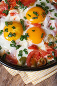 Fried eggs with tomatoes in a pan on the table vertical  macro  — Stock Photo