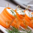 Rolls of fresh carrots with soft cheese on the table — Stock Photo #47408543