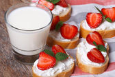 Sandwiches with soft cheese and fresh strawberries and milk — Stock Photo