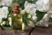 Bottle of fragrant jasmine essence closeup and flowers — Stockfoto