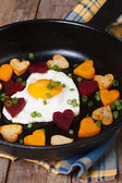 Egg in the form of heart in a pan with vegetables. Vertical — ストック写真