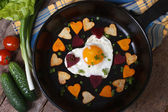 Egg and vegetables in the shape of heart — Photo