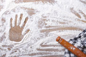 Handprint on the flour and rolling pin, a kitchen towel  — Stock Photo