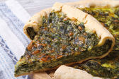 Pie with spinach and soft cheese on the table macro — Zdjęcie stockowe