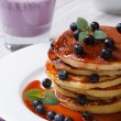 Blueberry pancakes with maple syrup and a cocktail close-up — Stock Photo #48360789